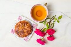 Το σπιτικό κέικ φεγγαριών με το τσάι και αυξήθηκε εξυπηρετημένος στον πίνακα Στοκ φωτογραφία με δικαίωμα ελεύθερης χρήσης