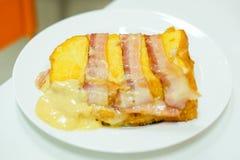 Το σπιτικό μπέϊκον και το ζαμπόν ` που τίθενται στο ψωμί με το τυρί ` τυριού Cheddar & μοτσαρελών εξυπηρετούν στο άσπρο πιάτο για Στοκ Φωτογραφίες