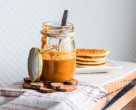Το σπιτικό φυστικοβούτυρο σε ένα βάζο γυαλιού, τρώει ένα κουταλάκι του γλυκού Στοκ Εικόνα