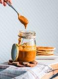 Το σπιτικό φυστικοβούτυρο σε ένα βάζο γυαλιού, τρώει ένα κουταλάκι του γλυκού Στοκ Εικόνες