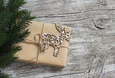 Το σπιτικό δώρο Χριστουγέννων στο έγγραφο του Κραφτ, ξύλινη διακόσμηση ελαφιών Χριστουγέννων, χριστουγεννιάτικο δέντρο διακλαδίζε Στοκ Φωτογραφία
