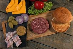 Το σπιτικό cheeseburger φρέσκο τυρί συστατικών, κουλούρι, αλάτισε το αγγούρι, patties βόειου κρέατος, μπέϊκον Στοκ εικόνες με δικαίωμα ελεύθερης χρήσης