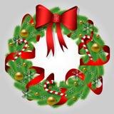 Το στεφάνι Χριστουγέννων του έλατου διακλαδίζεται με ένα τόξο, χρυσές σφαίρες, μια κόκκινη κορδέλλα, τις καραμέλες και snowflakes ελεύθερη απεικόνιση δικαιώματος