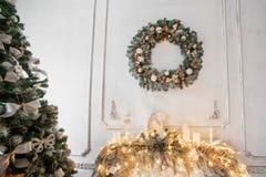 Το στεφάνι Χριστουγέννων του ελαιόπρινου με το λευκό υποκύπτει πέρα από την εστία, ένα άνετο χειμερινό πρωί Στοκ Εικόνα
