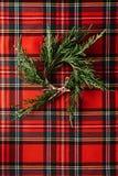 Το στεφάνι Χριστουγέννων του φρέσκου πεύκου διακλαδίζεται στο κόκκινο ελεγμένο ύφασμα, και το διάστημα αντιγράφων Εννοιολογικό υπ στοκ εικόνα με δικαίωμα ελεύθερης χρήσης