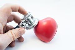 Το στηθοσκόπιο εκμετάλλευσης γιατρών στο χέρι του, εξετάζει τη μορφή καρδιών για την παρουσία ασθενειών του καρδιαγγειακού συστήμ Στοκ Φωτογραφίες