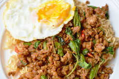 Το στιγμιαίο κάλυμμα νουντλς πικάντικο ανακατώνει το τηγανισμένα χοιρινό κρέας μπριζολών και το φύλλο βασιλικού με το αυγό Στοκ Εικόνες
