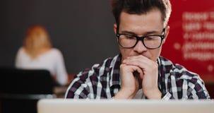 Το στοχαστικό άτομο κάθεται στο lap-top στο γραφείο απόθεμα βίντεο