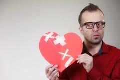 Το στοχαστικό άτομο κρατά τη σπασμένη καρδιά στοκ φωτογραφίες