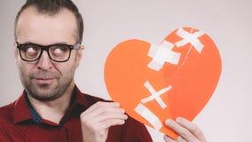 Το στοχαστικό άτομο κρατά τη σπασμένη καρδιά στοκ εικόνα