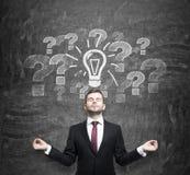 Το στοχαστικό άτομο ψάχνει τις καλύτερες επιχειρησιακές ιδέες να αρχίσει μια νέα επιχείρηση Τα ερωτηματικά και μια λάμπα φωτός εί στοκ εικόνα