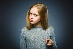 Το στοχαστικό ή περιφρονητικό κορίτσι κινηματογραφήσεων σε πρώτο πλάνο παρουσιάζει στη κάμερα που απομονώνεται σε γκρίζο Στοκ Εικόνες
