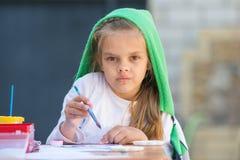 Το στοχαστικό και ενθουσιώδες κορίτσι σύρει μια ζωγραφική στον πίνακα και εξετασμένος το πλαίσιο στοκ εικόνες