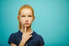 Το στοχαστικό κορίτσι δεκάχρονων παιδιών με την κόκκινη τρίχα βάζει το δάχτυλό της στο πηγούνι, ανατρέχει, εκφράζει την ανησυχία  στοκ φωτογραφία