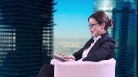 Το στούντιο TV Η επιχειρησιακή γυναίκα με τα γυαλιά που κάθεται στο στούντιο σε ένα επιχειρησιακό κοστούμι και δίνει τις συνεντεύ απόθεμα βίντεο