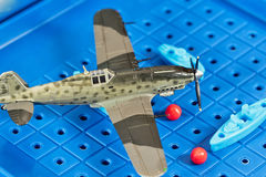 Το στρατιωτικό αεροπλάνο παιχνιδιών επιτίθεται στα σκάφη παιχνιδιών Στοκ Φωτογραφία