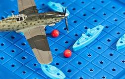 Το στρατιωτικό αεροπλάνο παιχνιδιών επιτίθεται στα σκάφη παιχνιδιών Στοκ Φωτογραφίες