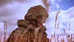 Το στρατιωτικό καυκάσιο άτομο στην κάλυψη στέκεται σε ένα γόνατο, κρατώντας το αυτόματο πυροβόλο όπλο, που περιβάλλονται με την υ φιλμ μικρού μήκους