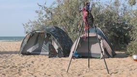 Το στρατόπεδο τουριστών, οι σκηνές και ένα αυτοκίνητο είναι στο χώρο στάθμευσης τουριστών Στο τρίποδο της κίνησης μαγιό ένωσης φω απόθεμα βίντεο