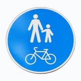 Το στρογγυλός-διαμορφωμένο οδικό σημάδι είναι μια ζώνη πεζών και ποδηλάτων Οι λευκοί άνθρωποι υπογράφουν και ποδήλατο σε ένα μπλε στοκ εικόνα