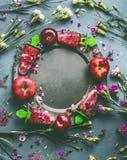 Το στρογγυλό πλαίσιο κύκλων του σπιτικού κόκκινου παγωτού ή Popsicle φρούτων μούρων στο πιάτο στο επιτραπέζιο υπόβαθρο κουζινών μ Στοκ Φωτογραφίες
