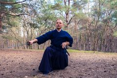 Το συγκεντρωμένο άτομο με ένα ξίφος, katana ασκεί τις πολεμικές τέχνες Στοκ Φωτογραφία