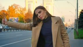 Το συγκεντρωμένο καυκάσιο θηλυκό στέκεται κατά μέρος το δρόμο με την κίνηση του αυτοκινήτου και κάνοντας ωτοστόπ με την παραδώστε απόθεμα βίντεο