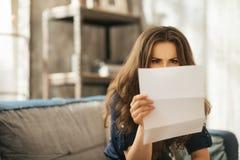 Το συγκεντρωμένο νέο θηλυκό κάθεται στην επιστολή ανάγνωσης καναπέδων Στοκ Φωτογραφία