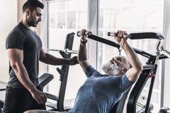 Το συγκεντρωμένο παλαιό αρσενικό έχει workout με τον εκπαιδευτή του στοκ φωτογραφία