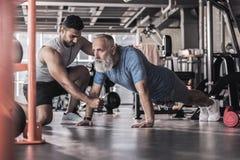 Το συγκεντρωμένο παλαιό αρσενικό έχει workout στο αθλητικό κέντρο στοκ εικόνες