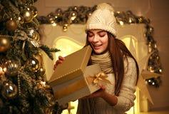 Το συγκινημένο κορίτσι ανοίγει το δώρο Χριστουγέννων στο σπίτι στο ντεκόρ του νέου έτους στοκ φωτογραφία με δικαίωμα ελεύθερης χρήσης