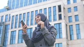 Το συγκινημένο μουσουλμανικό κορίτσι διαβάζει το μήνυμα στο τηλέφωνο για την εργασία που μισθώνει ή που μπαίνει στο κολλέγιο απόθεμα βίντεο