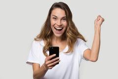 Το συγκινημένο smartphone εκμετάλλευσης γυναικών αισθάνεται την ενθουσιασμένη νίκη εορτασμού στοκ φωτογραφία με δικαίωμα ελεύθερης χρήσης