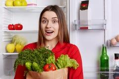 Το συγκλονισμένο έκπληκτο νέο θηλυκό φορά την κόκκινη μπλούζα, κρατά τα διάφορα λαχανικά στο κιβώτιο χαρτοκιβωτίων, στέκεται ενάν Στοκ φωτογραφία με δικαίωμα ελεύθερης χρήσης