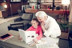 Το συναίσθημα εγγονών περιέλαβε στην ανάγνωση του βιβλίου με τη γιαγιά στοκ φωτογραφία