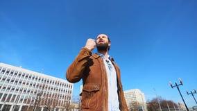 Το συναισθηματικό άτομο που μιλά σε ένα smartphone και είναι ενάντια σε έναν μπλε ουρανό απόθεμα βίντεο