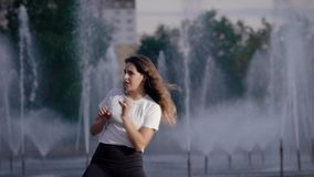 Το συναισθηματικό αισθησιακό κορίτσι χορεύει σε μια οδό της πόλης στην ημέρα μπροστά από τις πηγές, σύγχρονος χορευτής φιλμ μικρού μήκους
