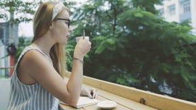 Το συναισθηματικό θηλυκό γράφει στο σημειωματάριο και τον καφέ κατανάλωσης στον καφέ απόθεμα βίντεο