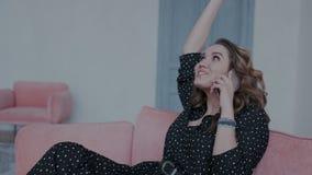 Το συναισθηματικό και γοητευτικό κορίτσι κάθεται στον καναπέ και ομιλία για τις καλές ειδήσεις στο κινητό τηλέφωνό της Είναι ευτυ φιλμ μικρού μήκους