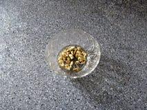 Το συντριμμένο σκόρδο στέκεται σε ένα κύπελλο γυαλιού στην γκρίζα επισημασμένη επιφάνεια του πίνακα Στοκ εικόνες με δικαίωμα ελεύθερης χρήσης