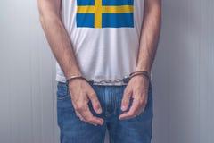 Το συλλήφθείτ άτομο με τα χέρια που φορούν το πουκάμισο με τη σουηδική σημαία Στοκ Εικόνες