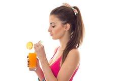 Το σχεδιάγραμμα του νέου όμορφου κοριτσιού brunette στο ρόδινο πουκάμισο πίνει το πορτοκαλί κοκτέιλ και το χαμόγελο στη κάμερα πο Στοκ φωτογραφίες με δικαίωμα ελεύθερης χρήσης