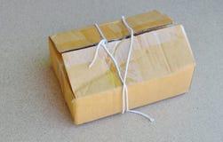 Το σχοινί δεμάτων έκοψε και ανοίγει το καφετί ταχυδρομικό κουτί Στοκ Εικόνες