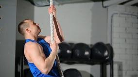 Το σχοινί ικανότητας αναρριχείται στην άσκηση στη γυμναστική Workout ικανότητας Νέος αρσενικός αθλητής φιλμ μικρού μήκους