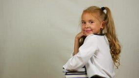 Το σχολικό κορίτσι σε ομοιόμορφο κάθεται τους αγκώνες στα βιβλία και το χαμόγελο στη κάμερα Πλάγια όψη φιλμ μικρού μήκους