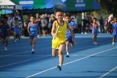 Το σχολικό αγόρι τρέχει κατά τη διάρκεια της φυλής ηλεκτρονόμων του φεστιβάλ αθλητικής ημέρας στοκ εικόνα