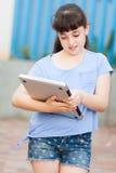 Το σχολικό κορίτσι με κρατά την ταμπλέτα Στοκ Φωτογραφία