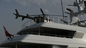 Το σύγχρονο γιοτ με το ελικόπτερο στην κορυφή στη μαρίνα γιοτ απόθεμα βίντεο