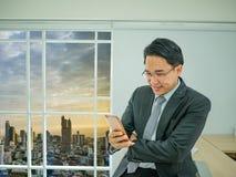 Το σύγχρονο επιχειρησιακό άτομο ελέγχει το κινητό τηλέφωνό του στοκ φωτογραφία