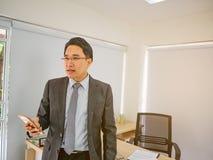 Το σύγχρονο επιχειρησιακό άτομο φαίνεται σοβαρό στο γραφείο του στοκ φωτογραφίες